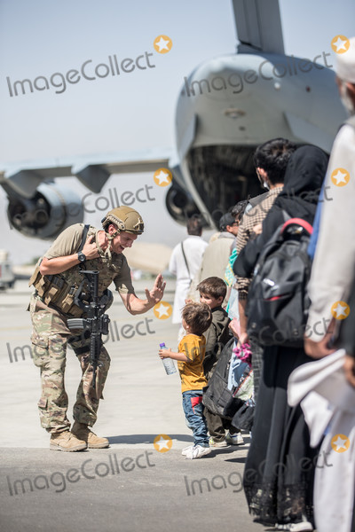Afghanistan Evacuation Photo - A United States Marine with Special Purpose Marine Air-Ground Task Force-Crisis Response-Central Command (SPMAGTF-CR-CC) gives a child a fist bump during an evacuation at Hamid Karzai International Airport Kabul Afghanistan August 24 2021 US service members are assisting the Department of State with an orderly drawdown of designated personnel in Afghanistan Mandatory Credit Samuel Ruiz  US Marine Corps via CNPAdMedia