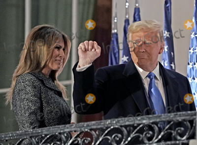 The Ceremonies Photo - United States President Donald J Trump gestures to guests as he and First lady Melania Trump return to the Residence following the ceremony where Justice Amy Coney Barrett took the oath of office to be Associate Justice of the Supreme Court on the Blue Room Balcony of the White House in Washington DC US October 26 2020 Credit Ken Cedeno  Pool via CNPAdMedia