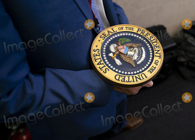 Mark Andes Photo - Communications staff carries away the presidential seal after President Donald Trump delivered remarks on the stock marked and the Dow reaching 30000 for the first time in history at the White House in Washington DC on Tuesday November 24 2020 Credit Kevin Dietsch  Pool via CNPAdMedia