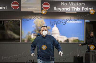 The Interns Photo - A man wears a protective mask as he and other passengers arrive from Dubai after a 14-hour flight on Emirates flight 231 at the international terminal at Dulles International Airport in Dulles Va Monday March16 2020 Some people are taking the precaution of wearing face masks as they arrive to be greeted by family and or friends Credit Rod Lamkey  CNPAdMedia