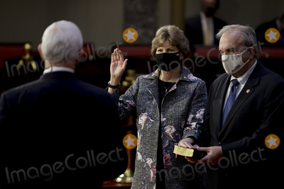 Jeanne Shaheen Photo - United States Senator Jeanne Shaheen (Democrat of New Hampshire) center wears a protective mask while being ceremoniously sworn-in by US Vice President Mike Pence left with husband Bill Shaheen at the US Capitol in Washington DC US on Sunday Jan 3 2021 The 117th Congress begins today with the election of the speaker of the House and administration of the oath of office for lawmakers in both chambers procedures that will be modified to account for Covid-19 precautions Credit Samuel Corum  Pool via CNPAdMedia