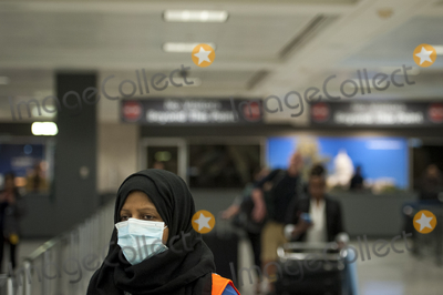 The Interns Photo - A Dulles International Airport worker assists passengers as they arrive from Dubai after a 14-hour flight on Emirates flight 231 at the international terminal at Dulles International Airport in Dulles Va Monday March16 2020 Some people are taking the precaution of wearing face masks as they arrive to be greeted by family and or friends Credit Rod Lamkey  CNPAdMedia