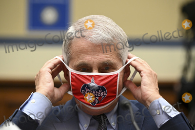 The National Photo - Anthony Fauci director of the National Institute of Allergy and Infectious Diseases removes his Washington Nationals protective mask during a US House Select Subcommittee on the Coronavirus Crisis hearing in Washington DC US on Friday July 31 2020 Trump administration officials are set to defend the federal governments response to the coronavirus crisis at the hearing hosted by a House panel calling for a national plan to contain the virus Credit Erin Scott  Pool via CNPAdMedia