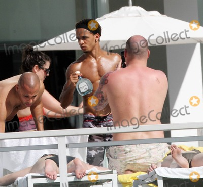 Aston Merrygold Photo - EXCLUSIVE JLS members Aston Merrygold and Marvin Humes celebrate the end of their sold out UK arena tour with a holiday in the Miami sun  The pals looked like they were having a blast as they sunbathed shirtless showing off their toned torsos posed for photographs with a female fan and enjoyed a bottle of Don Julio Tequila and pink champagne with friends in the Florida sunshine at their exclusive waterfront hotel  A tattooed Aston also chatted for a while on his mobile phone Miami Beach FL 2411Fees must be agreed prior to publication