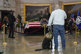 Photo - A man with a service dog pays respects to slain US Capitol Police officer William Billy Evans as he lies in honor at the Capitol in Washington Tuesday April 13 2021 Credit Jacquelyn Martin  Pool via CNPAdMedia