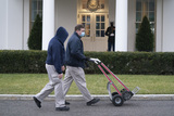 Photos From Workers with empty hand trucks pass the West Wing
